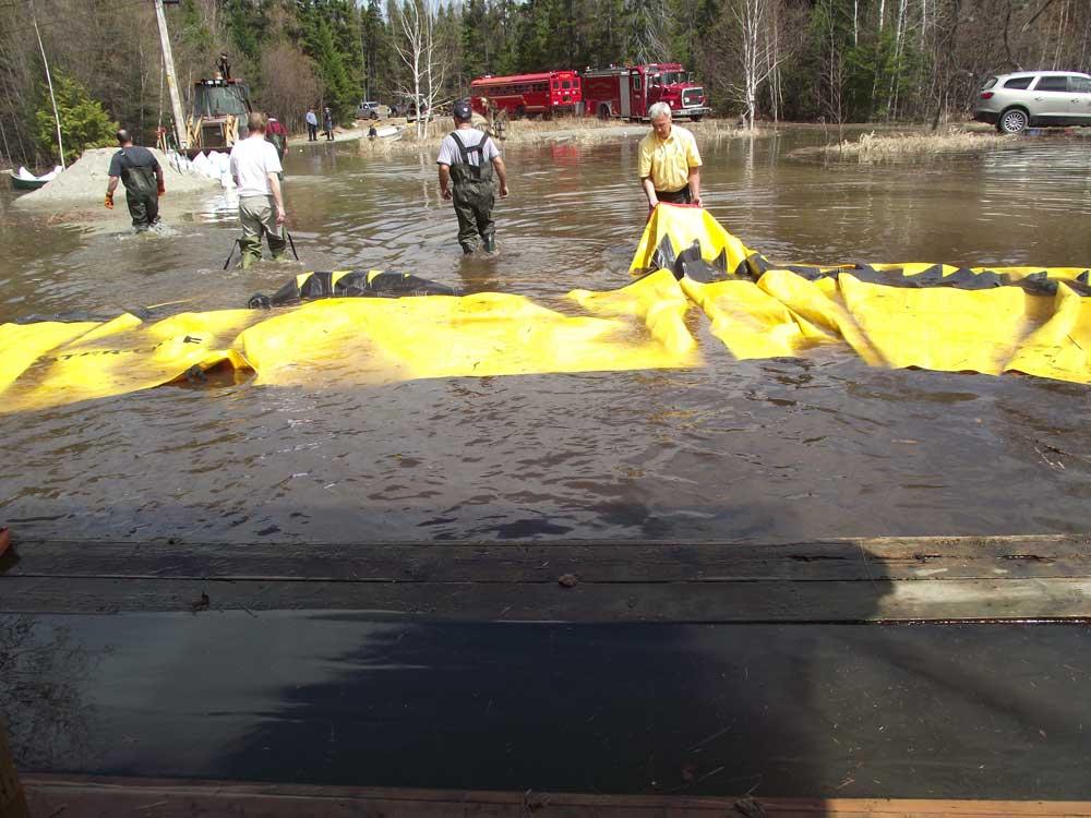 installation d'un barrage anti inondation au tour d'une maison déjà inondée