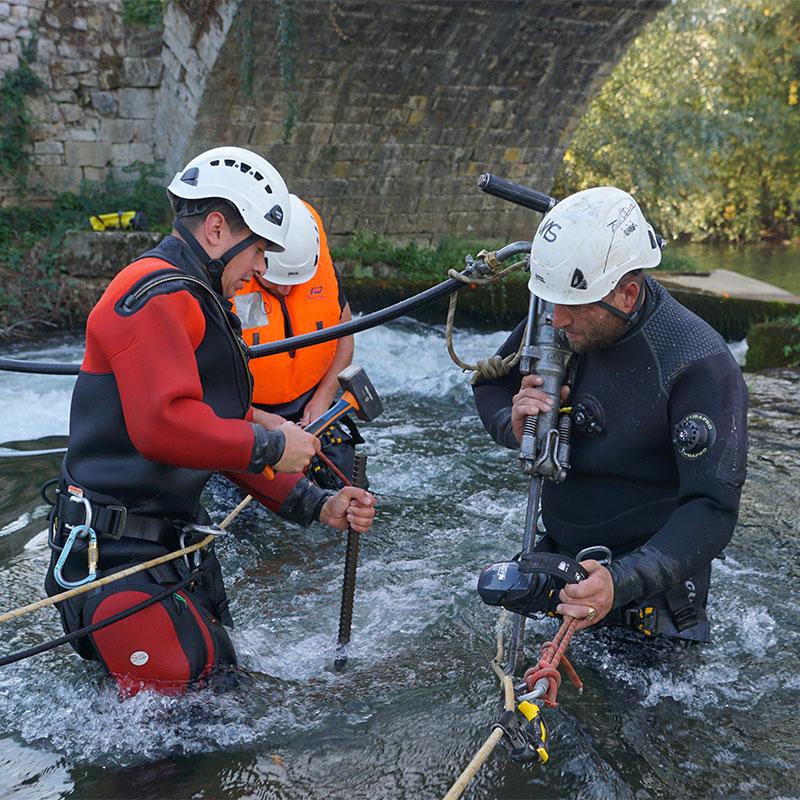 Travaux rivière. Installation de butées anti-glissement pour batardeau souple water-gate.