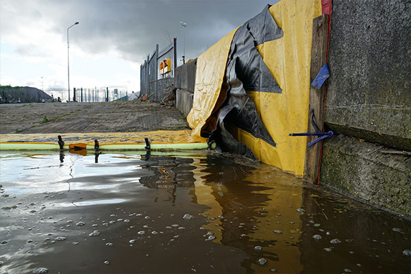 Barrage souple Water-Gate© appuyé contre un mur. On fixe le bord d'attaque avec une planche pour réduire les fuites lors de la mise en eau.