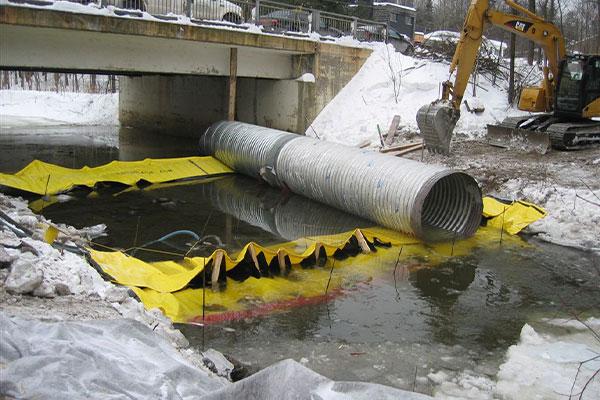 Installation de deux batardeaux Water-Gate© tête bêche avec tube de dérivation placé sur les barrages flexibles.