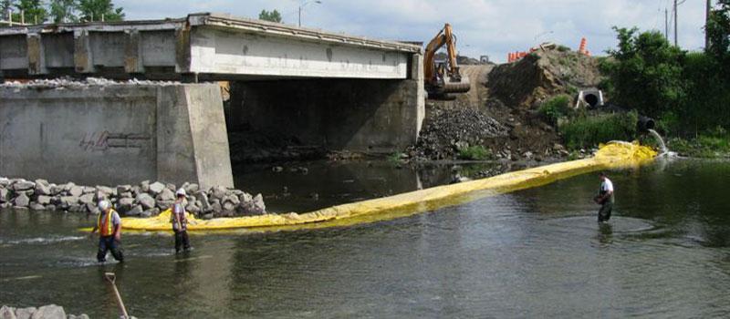 Travaux de réparation sur un pont en deux phases. Installation d'un batardeau souple en L depuis chaque berge.