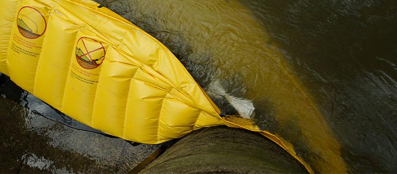 Appui d'une extrémité de batardeau souple Water-Gate©contre une pile de pont. Le batardeau épouse la forme du support.