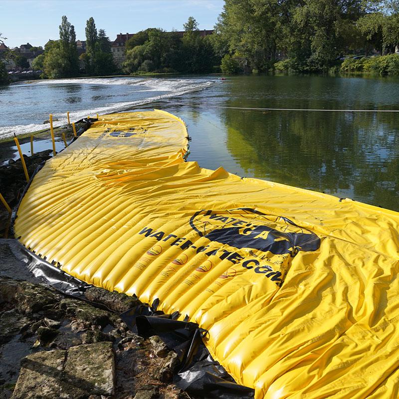 Assèchement d'un bras de rivière sur le Doubs. Le batardeau souple est positionné en rive gauche dans le prolongement du seuil de Dole.