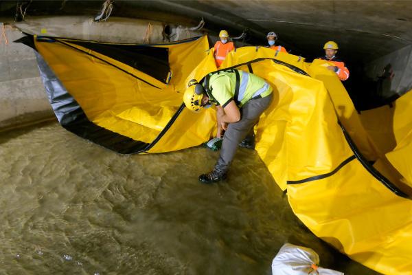 Poser au sol sous le barrage souple Water-Gate© des bûches de gravier pour augmenter les forces de friction.