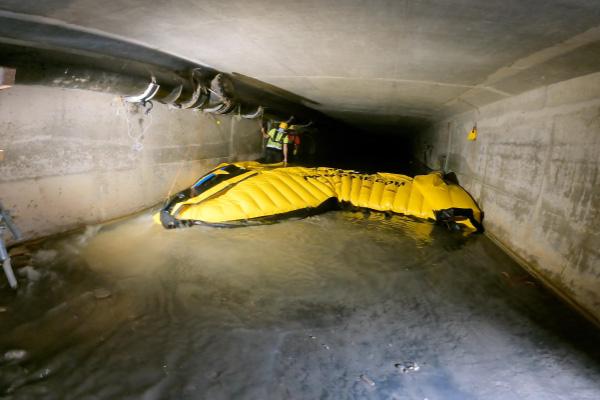 Dépose d'un batardeau souple Water-Gate©. On soulève le bord d'attaque pour faire passer l'eau sous le batardeau et réduire les forces de friction.